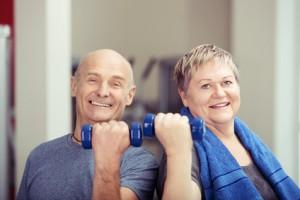 älteres paar trainiert mit kleinen hanteln im fitnessraum